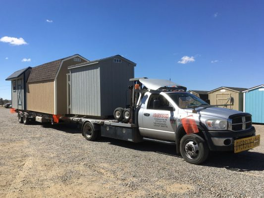 Delivery truck and trailer loaded with barns and sheds
