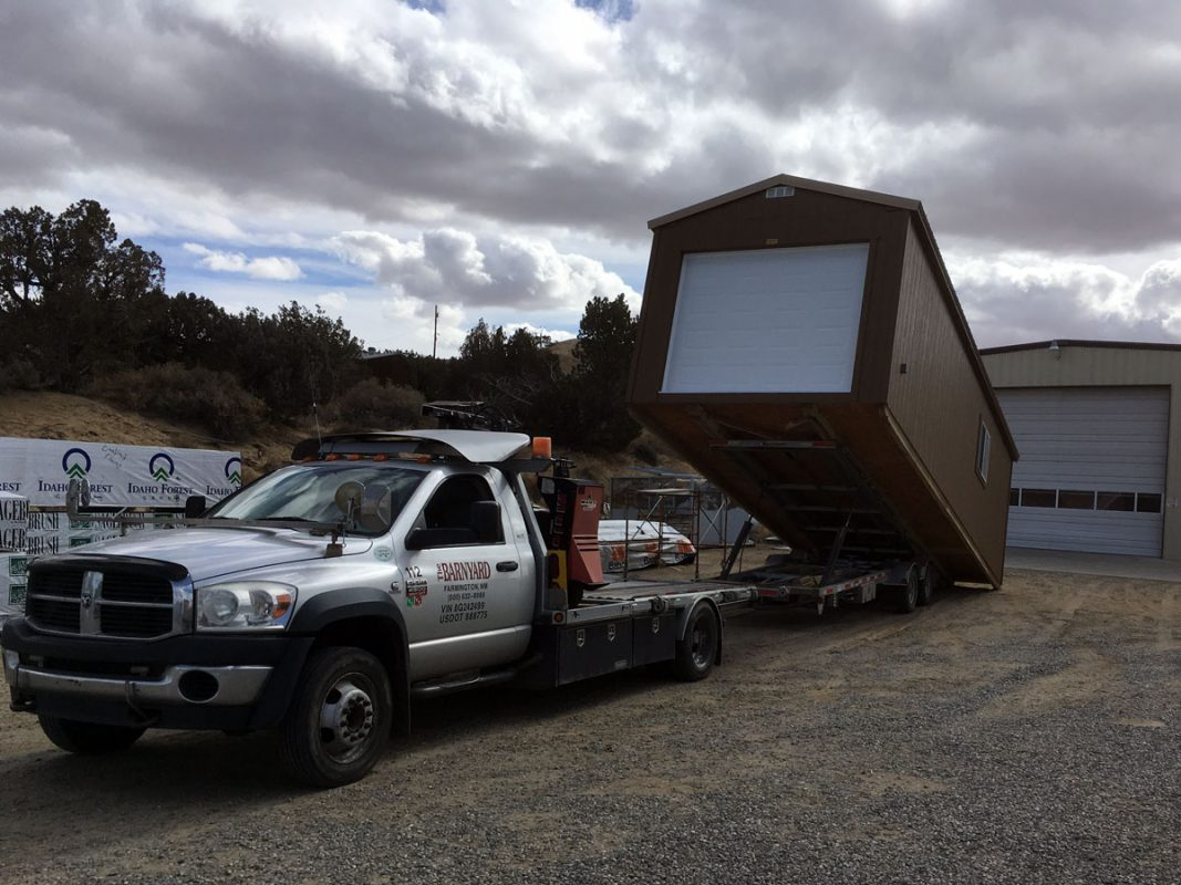 Unloading a ranch-style garage from a delivery trailer
